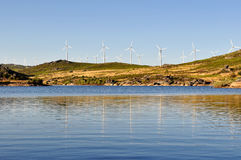 Wind Turbines. Wind mill, with several wind turbines, near a river, producing green energy Royalty Free Stock Photo