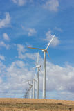 Wind turbines. In a row against cloudy sky Royalty Free Stock Images