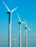 Wind Turbines. Modern white wind turbines or wind mills producing energy to power a city Royalty Free Stock Photos