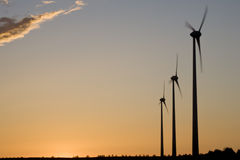 Wind turbines. Silhouettes of wind turbines on sunset sky background (Horizontal Axis Wind Turbine HAWT Royalty Free Stock Images