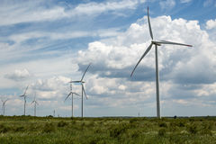 Wind turbines against beautiful cloudy sky. Renewable energy production stock images