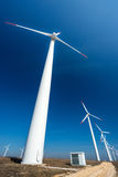 Wind turbines  against a blue sky generating electricity Royalty Free Stock Images
