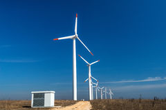 Wind turbines  against a blue sky generating electricity Royalty Free Stock Image