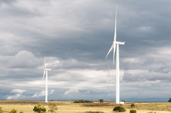 Wind turbines against dark clouds Royalty Free Stock Photos