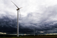 Wind turbines against dark clouds in the upcoming storm, concept Stock Images