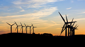 Wind turbines against sunset. Silhouette of wind turbines against a sunset royalty free stock images