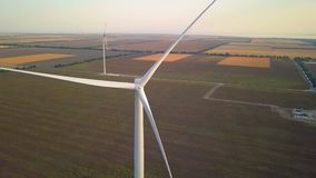 Wind turbines and agricultural fields on a summer day - Energy Production with clean and Renewable Energy - aerial shot.  stock video