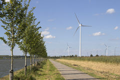 Wind turbines along a channel on a sunny day. Wind turbines generating electricity along a channel on a sunny day Royalty Free Stock Photos