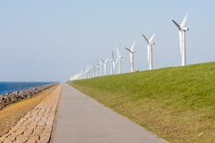 Wind turbines along a Dutch dike Stock Photo