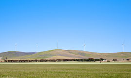 Wind turbines along hill Royalty Free Stock Photography