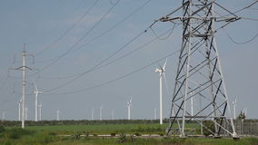 Wind turbines in the background with power lines carrying electricity in foreground. Power lines on the background of wind power stock video