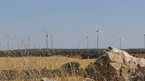Wind Turbines on a Background of Stone in the Desert of Spain. Massive wind turbines generating power. Heat haze effect on desert land. Clean Energy producing stock footage