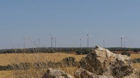 Wind Turbines on a Background of Stone in the Desert of Spain. Massive wind turbines generating power. Heat haze effect on desert land. Clean Energy producing stock video