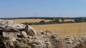 Wind Turbines on a Background of Stone in the Desert of Spain. Massive wind turbines generating power. Heat haze effect on desert land. Clean Energy producing stock video footage