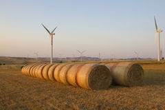 Wind turbines and bales of hay in a field. In a sunny day Stock Images