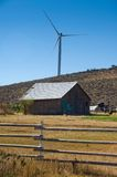 Wind turbines behind a farm building. Royalty Free Stock Image