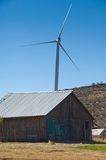 Wind turbines behind a farm building. Royalty Free Stock Photos
