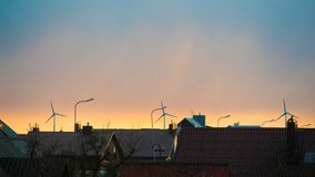 Wind turbines behind roofs. In the morning Stock Photo