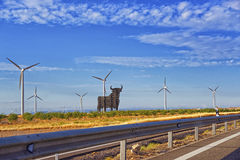 Wind turbines and black bull shape in front of blue sky Stock Photo