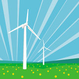 Wind turbines and blue sky. Wind turbines among green grass and flowers against the blue sky background Royalty Free Stock Images