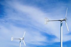 Wind turbines on blue sky. White Wind turbines on bright fresh blue sky royalty free stock image