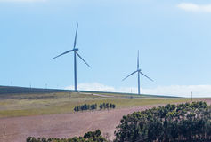 Wind turbines with clouds in the background and trees in the foreground. Stock Photos