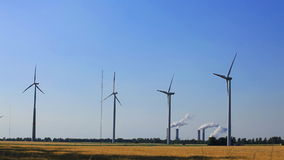 Wind turbines with coal fired power plant stock video footage