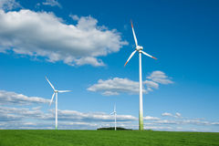 Wind turbines in countryside. Scenic view of wind turbine farm in countryside under blue sky and cloudscape Royalty Free Stock Image