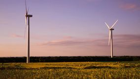 Wind turbines in the countryside under a beautiful sunset. Silhouettes of wind turbines in the countryside under a beautiful sunset stock video