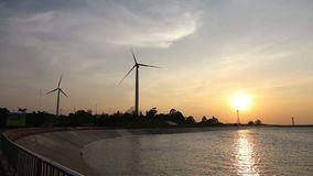 Wind turbines creating green energy with reservoir. At sunset stock video footage