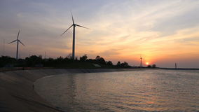 Wind turbines creating green energy with reservoir. At sunset stock video