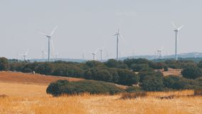 Wind Turbines in the Desert of Spain. Massive wind turbines generating power. Heat haze effect on desert land. Clean Energy producing of Windmills. Alternative stock footage