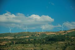 Wind turbines for electric power generation on hill. Some wind turbines for electric power generation on green hilly landscape with rocks, in a sunny day at stock photo