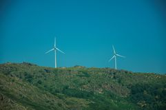 Wind turbines for electric power generation over hill. Wind turbines for electric power generation over green hilly landscape with rocks, in a sunny day at Serra royalty free stock image