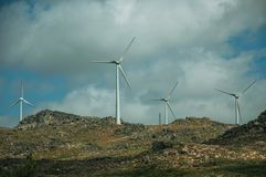 Wind turbines for electric power generation over hills. Wind turbines for electric power generation over green hilly landscape with rocks, in a sunny day near stock photo