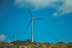 Wind turbines for electric power generation over hills. Wind turbines for electric power generation over green hilly landscape with rocks, in a sunny day near royalty free stock photography