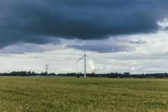 Wind turbines for electrical power generation in green agricultural fields in Normandy, France. Renewable energy sources. Industrial agriculture concept Stock Image