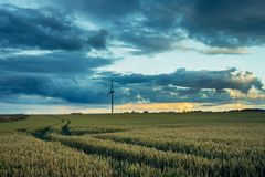 Wind turbines for electrical power generation in green agricultural fields in Normandy, France. Renewable energy sources. Industrial agriculture concept Stock Photography