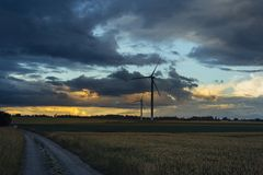 Wind turbines for electrical power generation in green agricultural fields in Normandy, France. Renewable energy sources. Industrial agriculture concept Royalty Free Stock Photo