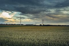 Wind turbines for electrical power generation in green agricultural fields in Normandy, France. Renewable energy sources. Industrial agriculture concept Stock Photos