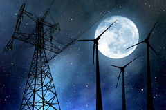 Wind turbines and electricity pylon in the night sky Stock Images