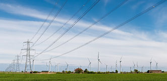 Wind turbines and electricity pylons. Wind turbines with electricity pylons intersecting the field in England. A commentary on renewable energy generation Royalty Free Stock Photos