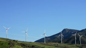 Wind turbines energy towers moving in the mountains with blue sky stock video footage