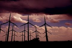 Wind Turbines Farm. After Dark. Pinky Stormy Sky and Wind Turbines Royalty Free Stock Photos