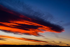 Wind Turbines Farm In The Distance On Beautiful Red, Orange And Blue Sunset Royalty Free Stock Image