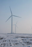 Wind turbines farm on field with fog and snow. In cold winter day Royalty Free Stock Images