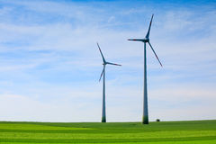 Wind turbines farm in field over cloudy sky Royalty Free Stock Photos
