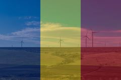 Wind turbines farm generating electricity covered by transparent Romania flag Stock Image