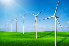 Wind turbines farm on a green grass hills royalty free stock images