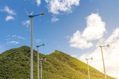 Wind turbines farm on mountanis landscape against blue sky with stock image